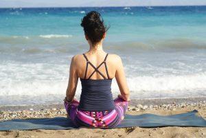 海に向かって瞑想する女性